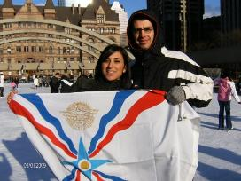 Assyrian flag held-up by a couple in Canada