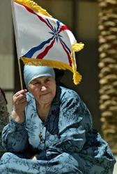 Assyrian flag held high by an elderly Assyrian woman in Ashur