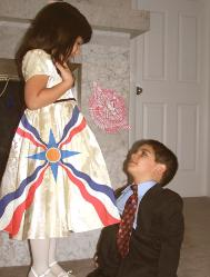 Assyrian flag skirt wore by a young Assyrian girl with a boy and Allaha Ashur